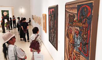 儀間比呂志さんの作品に見入る来場者=13日午前、那覇市の県立博物館・美術館(国吉聡志撮影)