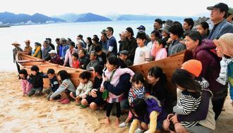 サバニを囲んで記念撮影する進水式の参加者=2日、名護市世紀の森ビーチ