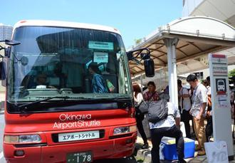 記念試乗会で沖縄エアポートシャトルに乗り込む乗客ら=23日、那覇市おもろまち