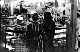 那覇市内にあった雑貨店の様子。庶民が日常的に生活物資を買い求めていた市場とは雰囲気が異なる。市内にいくつかあった百貨店内だろうか。店内にはキューピー人形がディスプレーされているほか、ボンタンアメの広告が確認できるなど、店の品ぞろえの豊富さが分かる。1935年当時から、沖縄にも商品経済の波が訪れていたことが見て取れる(写真:朝日新聞社)