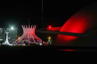 18日、日本国旗をイメージした色にライトアップされた大聖堂(左)と国立美術館=首都ブラジリア(ROBSON ANSELMO/在ブラジル日本大使館提供・共同)