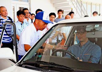 座席やハンドルを調整し、正しい運転姿勢を保持できるか、確認するべき指導のポイントについて解説する講師の黒澤明良さん(中央)=豊見城市・県警察運転免許センター