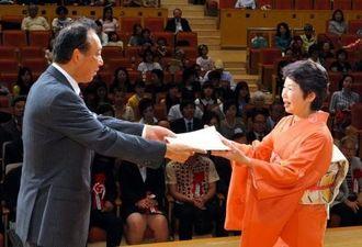 豊平良孝社長(左)から表彰される書芸部門準会員賞受賞の金城多美子さん=20日午後、浦添市てだこホール