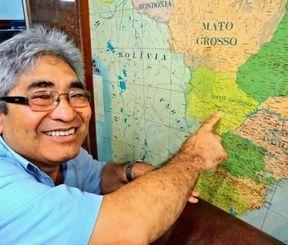 地図上のカンポグランデを指さす沖縄県人会会長の志良堂ニウトンさん