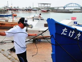 熱帯低気圧の接近を警戒し陸揚げした漁船をロープで固定する漁業者ら=22日、石垣市・登野城漁港