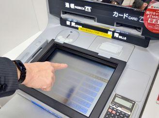 赤外線センサーで指の位置を検出する仕組みで、画面に触れずに操作できるATM=琉球銀行本店