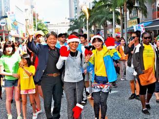 1964年の東京五輪の聖火リレーで第1走者を務めた宮城勇さん(前列左)ら=10日、那覇市・国際通り