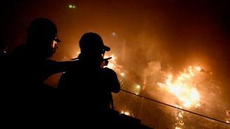炎上する香港理工大の構内を見つめる若者たち=18日早朝、香港(共同)