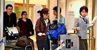 やや疲れた表情でターミナルを出る乗客=19日午前1時ごろ、那覇空港・国際線ターミナル