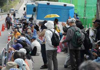 新基地建設反対を訴えキャンプ・シュワブゲート前で座り込む市民ら=22日午前、名護市辺野古