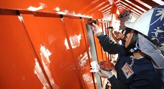首里城正殿の壁を塗り替える漆塗り職人。市場流通品の弁柄が使われていた=2010年11月2日、那覇市・首里城公園