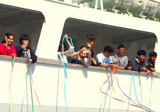 紙テープを投げ、渡名喜島に残る友人や先生らとの別れを惜しむ中学3年生ら=26日、渡名喜港