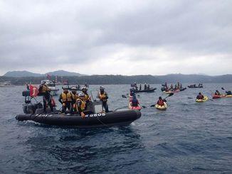 制限水域内に入った市民らのカヌーに対し、ゴムボート15艇を出して警戒する海上保安官ら=16日午前11時ごろ、名護市辺野古崎沖