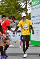 「京都マラソン2019」でゴールし、ランナーと握手する京都大iPS細胞研究所の山中伸弥所長(右)=17日、京都市