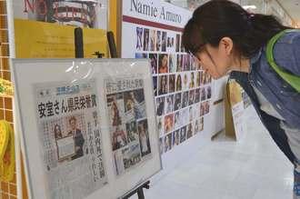 展示された安室奈美恵さんの号外に見入る女性=24日、那覇市久茂地・タワーレコード那覇リウボウ店