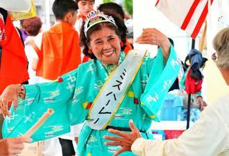 カチャーシーを踊るミスハーレーの新垣ヨシ子さん=6日、糸満漁港中地区(下地広也撮影)