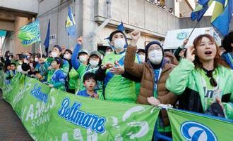 サッカーのJリーグが開幕し、選手を迎える湘南のサポーター。新型コロナウイルス感染予防のため、マスク姿の観客が目立った=21日、神奈川県平塚市のShonanBMWスタジアム平塚
