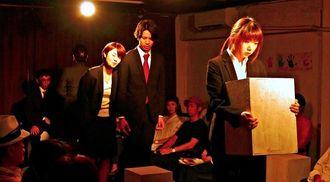 先輩からいじめを受ける、新入社員の崎原を演じるわたぬきかな(右端)=那覇市・わが街の小劇場