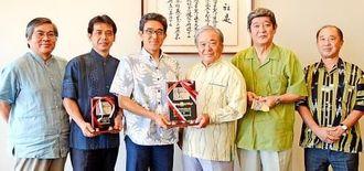 沖縄電力の本永浩之総務部長(左から3人目)から古波蔵廣県野球連盟会長(同4人目)に優勝盾が贈呈された=沖縄タイムス社