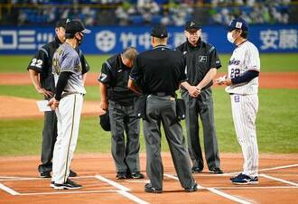 試合前のメンバー表交換の際、阪神・矢野監督(左手前)らに頭を下げる森審判員(左から3人目)=神宮