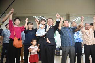 家族や支援者、議員とがんばろう三唱し、訪米に向けて気勢を上げる玉城デニー知事=14日午前10時20分、那覇空港1階ロビー