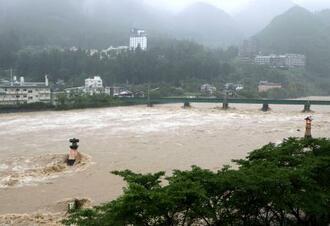 大雨により増水した飛騨川=8日午前7時28分、岐阜県下呂市
