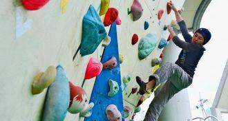 ウォールに取り付けられたボルダーをつかみ、ゴールを目指して登る=那覇市・奥武山公園