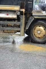 大雨で荷台から赤く濁った水が流れ出た大型トラック=13日午前、沖縄県名護市安和