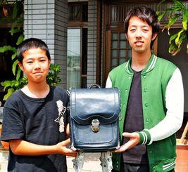 12年間使われたランドセルを手にする新里凜君(左)と兄の拓樹さん=21日、与那原町上与那原