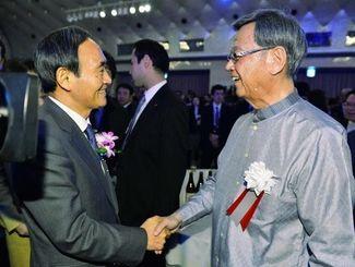 県の観光PRイベントで、来賓の菅官房長官(左)と握手する翁長雄志知事=27日夜、東京都港区