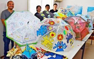 モノレール駅で展示されている作品の一部と、企画したNSPキングコングの仲地宗幸さん(左端)と従業員ら=12日、沖縄市泡瀬