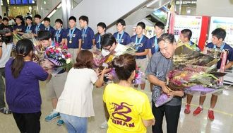優勝旗を手に凱旋し、父母会から花束を受け取る興南高校ハンドボール部=8日午後6時ごろ、那覇空港