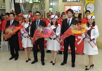 歓迎の花束を手にする広島カープの野村謙二郎監督(手前左から3人目)、前田健太(同5人目)ら=21日午後9時47分、那覇空港