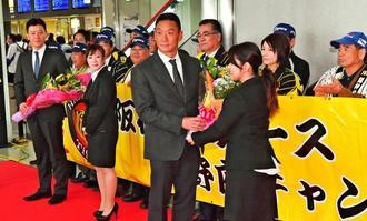 歓迎を受ける阪神の金本知憲監督(中央)ら=那覇空港