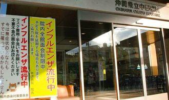インフルエンザの流行に注意を呼び掛ける県立中部病院の看板。院長名で、予定入院を延期する場合もあることが書かれている=1月23日午後、うるま市・沖縄県立中部病院