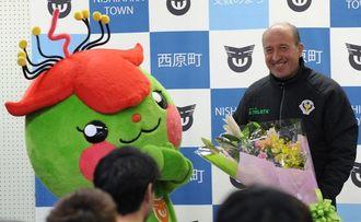 西原町の「さわりん」から花束を受け取るロティーナ監督(右)=西原町民陸上競技場