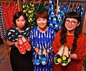 コラボの布靴を手にする(左から)上野晶子さんと後藤美由子さん、周薏如さん=台北市