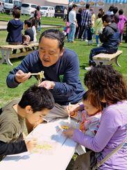 やえせグルメグランプリに出品された食事、スイーツを頬張る来場者ら=23日、八重瀬町の屋宜原中央公園