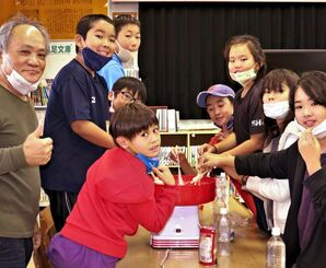 綿あめ製造機を囲む清水洋一教授(左)と阿嘉小中学校の子どもたち=12月19日、座間味村・同校