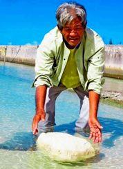 海に浮かぶ大きな石を見つけた波平恵喜さん=20日、多良間村