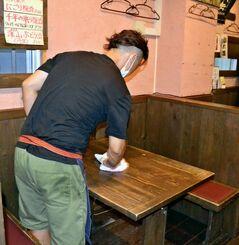 開店準備を始める那覇市内の飲食店店主。「これ以上の休業要請は受け入れられない」と嘆く=21日午後5時、那覇市
