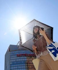 福岡・天神の繁華街を、日傘を差して歩く女性=23日