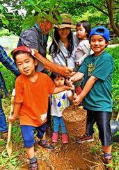 ドングリの木「アマミアラカシ」の苗木を植え付ける子どもたち=5日、那覇市の末吉公園
