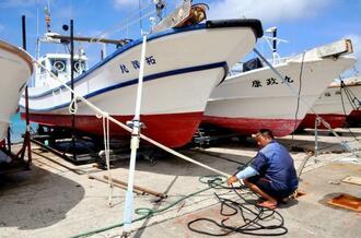 台風5号の接近を警戒し、陸揚げした漁船をロープで固定する漁業者=17日午前11時15分ごろ、石垣市登野城漁港