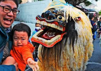 厄よけに頭をかもうとした獅子に驚いて泣きべそをかく幼児=1日、豊見城市の真玉橋団地自治会