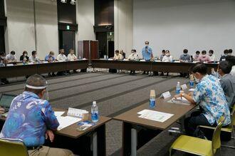 沖縄ツーリズム産業団体協議会であいさつする沖縄観光コンベンションビューローの下地芳郎会長と観光関連団体の代表ら=17日、県市町村自治会館