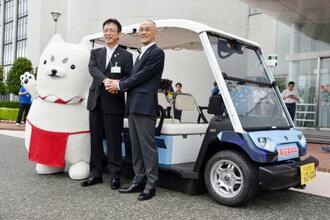 セレモニーで自動運転カートを背に握手するヤマハ発動機の日高祥博社長(右)と静岡県磐田市の渡部修市長=27日、同市