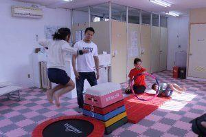 子どもたちと触れ合う須藤元気さん(左から2人目)と砂辺光久さん(同3人目)=15日、那覇市首里・クロスライン