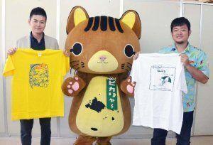 過去に採用されたTシャツを掲げ、応募を呼びかける青年部メンバーと竹富町のマスコット、ピカリャー=石垣市観光交流協会