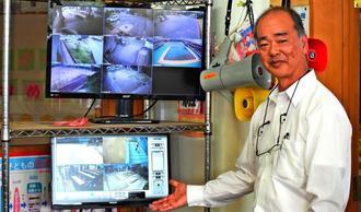 職員室に設置された映像などが確認できるパソコンについて説明する照屋校長=宜野湾小学校
